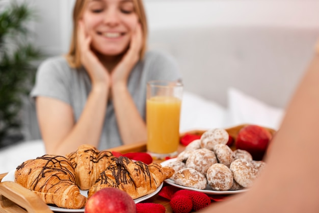 Smiley blurred woman being surprised with breakfast in bed Free Photo