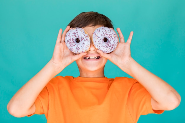 Smiley boy covering his eyes with doughnuts Free Photo