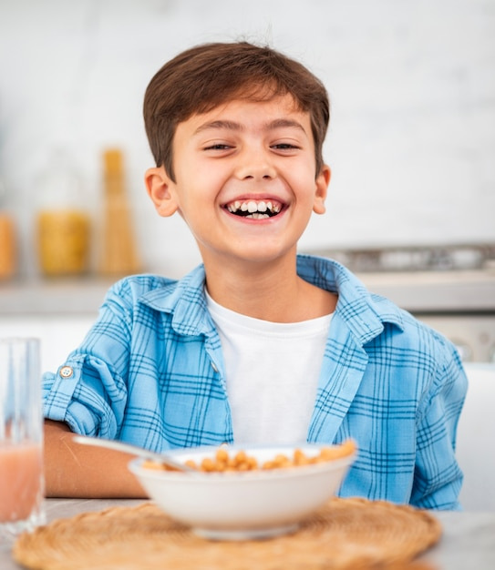 Smiley boy eating breakfast in the morning Free Photo