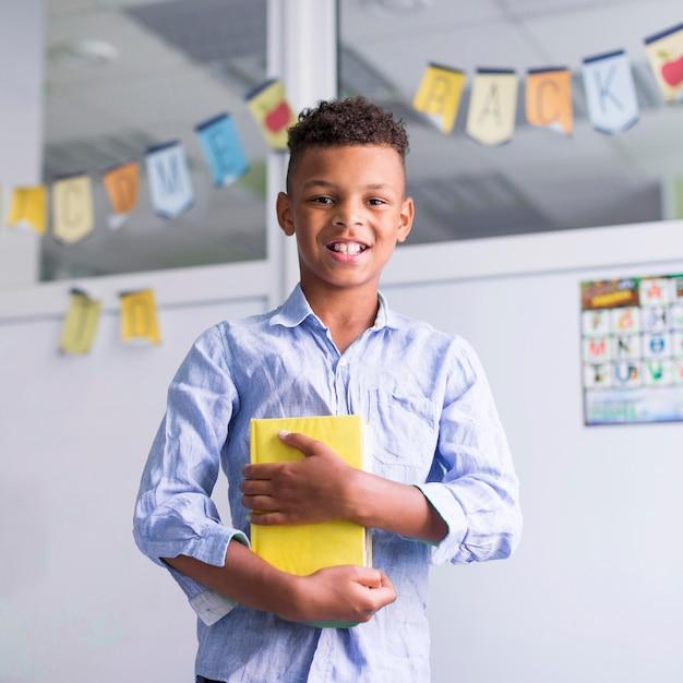 クラスで本を持っている笑顔の少年 無料写真