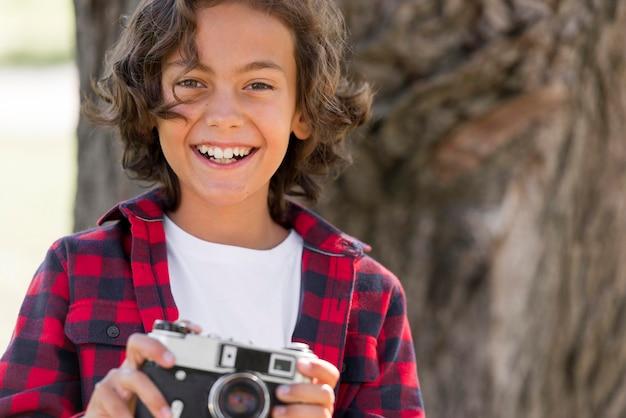 Смайлик мальчик держит камеру в парке Бесплатные Фотографии