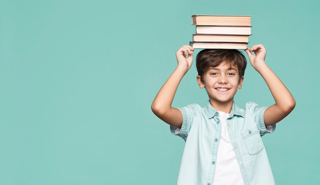 Smiley boy holding stack of books on head Free Photo