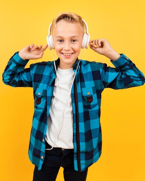 Smiley boy listening music at headphones Free Photo