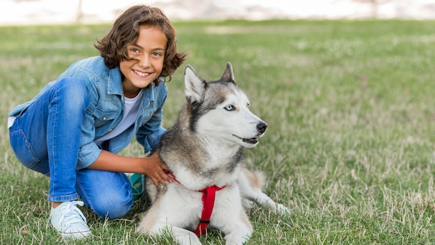 Улыбающийся мальчик позирует с собакой в парке Бесплатные Фотографии