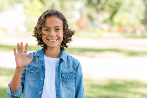 Улыбающийся мальчик машет рукой в парке Бесплатные Фотографии