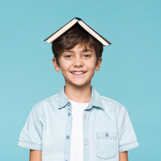 Smiley boy with book on head Free Photo