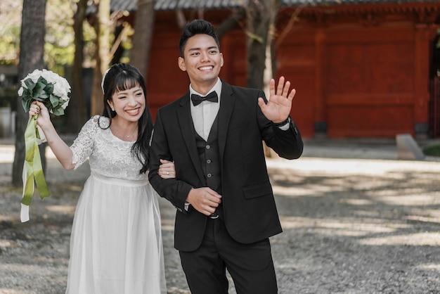 결혼 후 손을 흔드는 웃는 신부와 신랑 프리미엄 사진