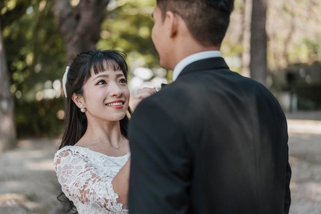 신랑의 나비 넥타이를 준비하는 웃는 신부 무료 사진