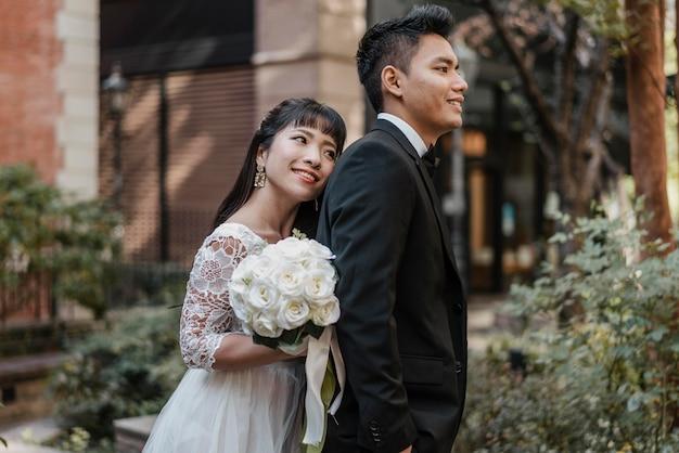 Sposa di smiley che si appoggia contro la parte posteriore dello sposo Foto Gratuite