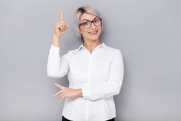 Smiley business woman pointing above Free Photo