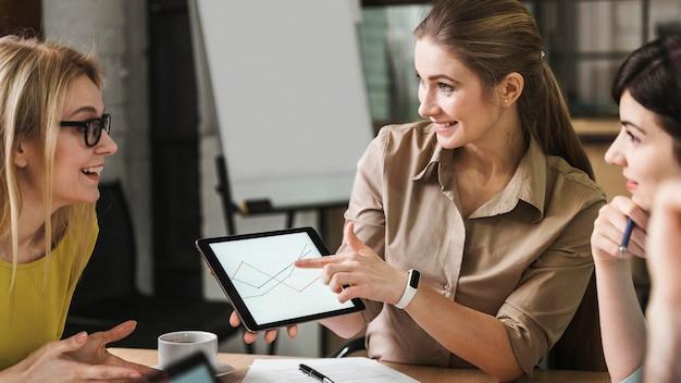 屋内での会議中にタブレットを使用するスマイリービジネスマン 無料写真