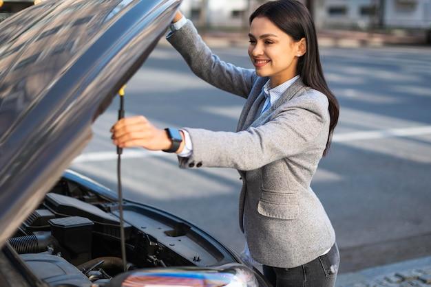 Смайлик бизнесвумен, поднимая капот автомобиля Бесплатные Фотографии