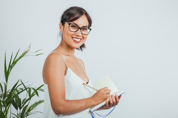 Smiley businesswoman posing and writing on her diary Free Photo