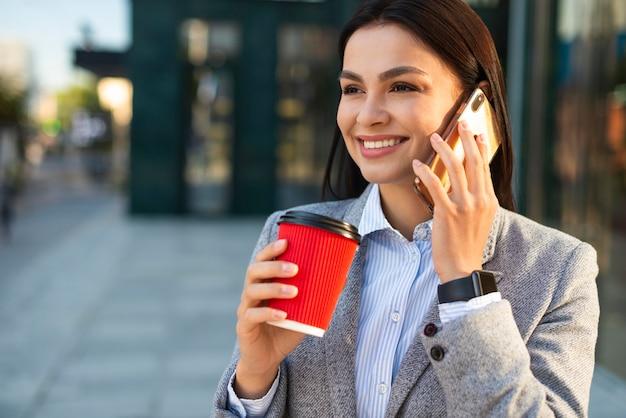 街でコーヒーを飲みながら電話で話しているスマイリー実業家 無料写真