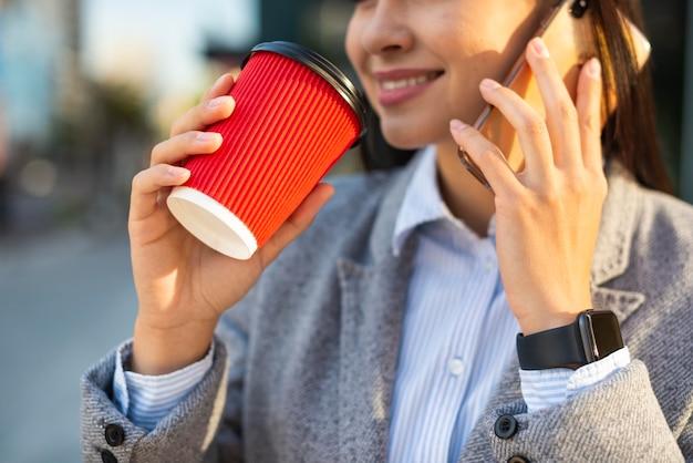 外でコーヒーを飲みながら電話で話しているスマイリー実業家 無料写真