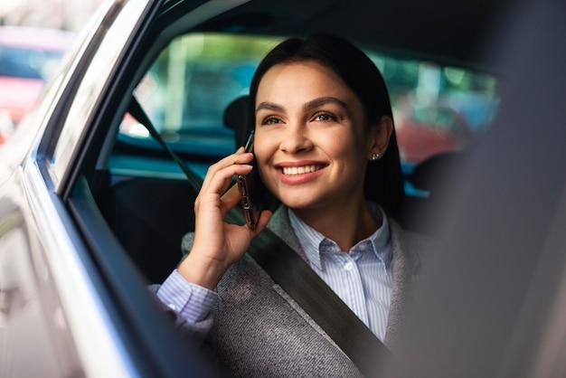 車の中で電話で話しているスマイリー実業家 Premium写真