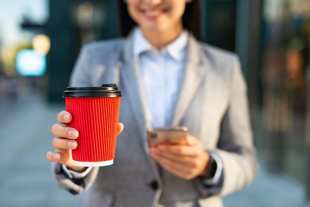 コーヒーを飲みながらスマートフォンを使用してスマイリー実業家 無料写真
