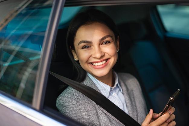 車の中でスマートフォンを持つスマイリー実業家 Premium写真