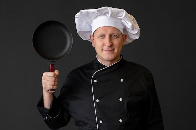鍋を持っているスマイリーシェフ 無料写真