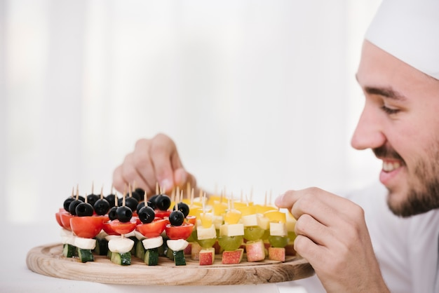 Smiley chef organizing plate of snacks Free Photo