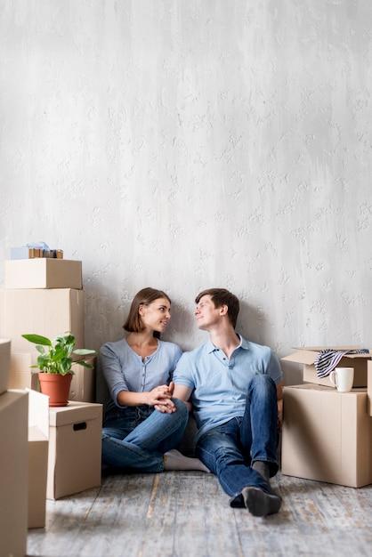 Улыбающаяся пара дома, собирая вещи, чтобы выехать Бесплатные Фотографии