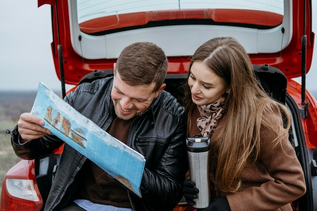 Смайлик пара проверяет карту в багажнике машины Бесплатные Фотографии