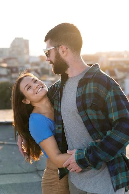 スマイリーカップルが街の屋外で抱擁 無料写真
