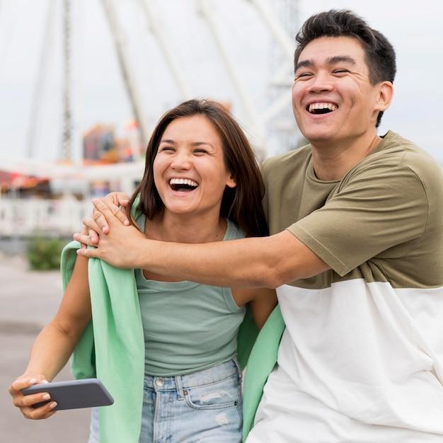 屋外で抱きしめたスマイリーカップル 無料写真