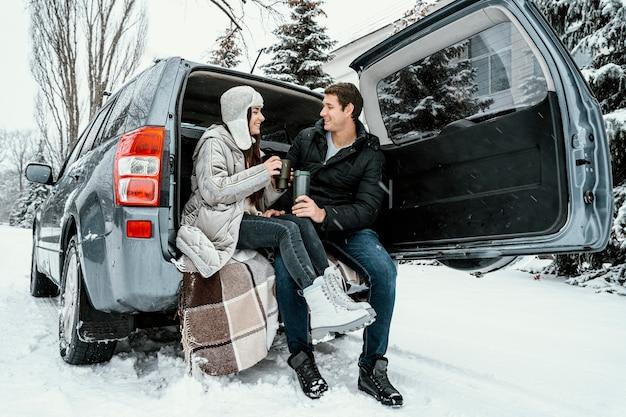 Улыбающаяся пара с теплым напитком в багажнике машины во время поездки Бесплатные Фотографии