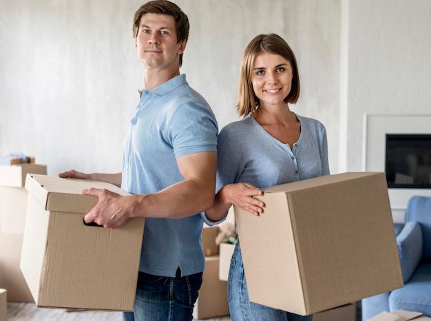 Смайлик пара, держащая коробки в день переезда Бесплатные Фотографии