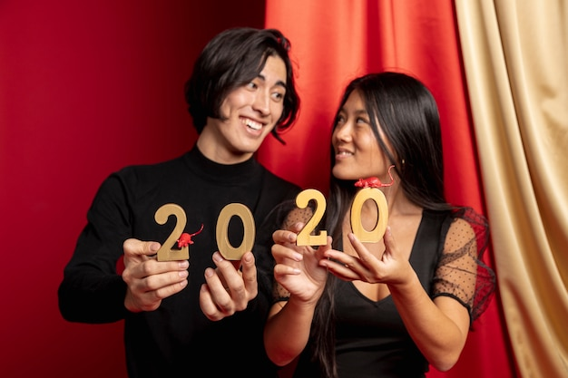 Smiley couple holding new year sign and rat figurines Free Photo
