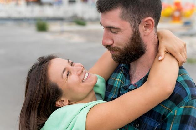 屋外で抱き締めるスマイリーカップル 無料写真