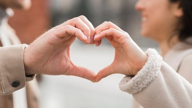 Le coppie di smiley che fanno il cuore modellano con le loro mani Foto Gratuite