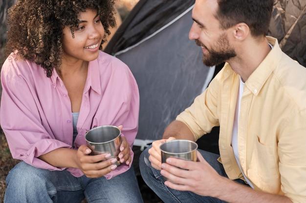 Coppia di smiley all'aperto con un drink Foto Gratuite