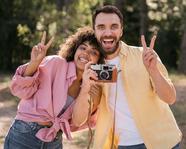 Coppia di smiley all'aperto scattare foto con la fotocamera Foto Gratuite