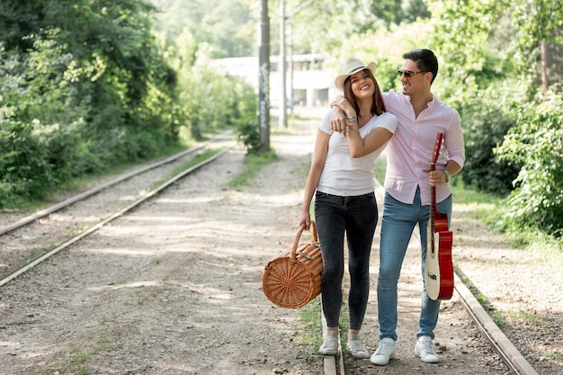 Smiley couple posing on railroad Free Photo