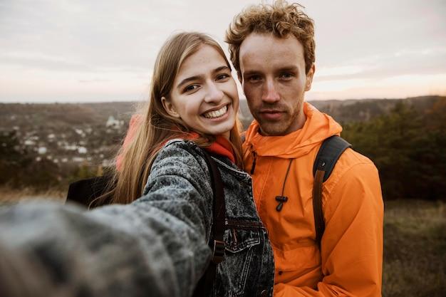 一緒にロードトリップ中に自分撮りをしているスマイリーカップル 無料写真