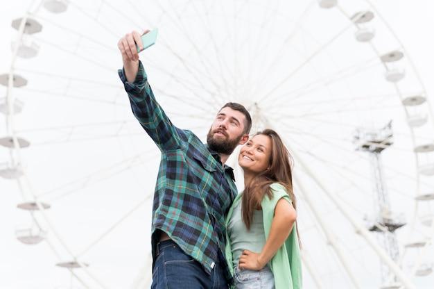 Смайлик пара, делающая селфи на открытом воздухе Бесплатные Фотографии