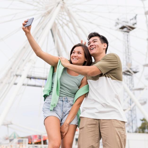 一緒に自分撮りをしているスマイリーカップル 無料写真