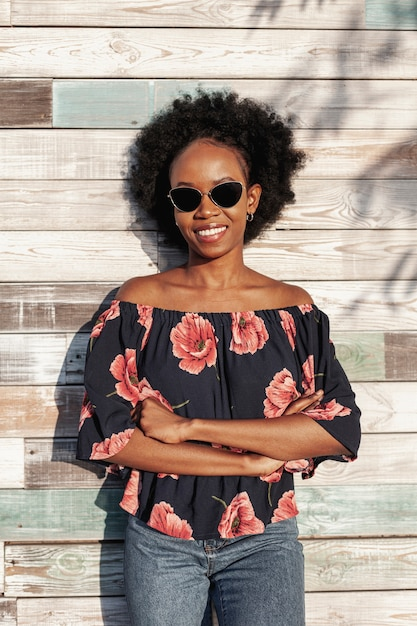 Smiley curly haired woman wearing sunglasses Free Photo