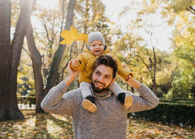 自然の中で彼の赤ちゃんと一緒にスマイリーのお父さん 無料写真