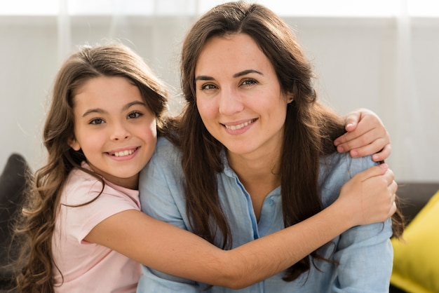 Smiley daughter hugging her mother in the living room Free Photo