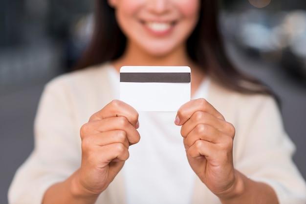 Смайлик расфокусированным женщина, держащая кредитную карту Бесплатные Фотографии