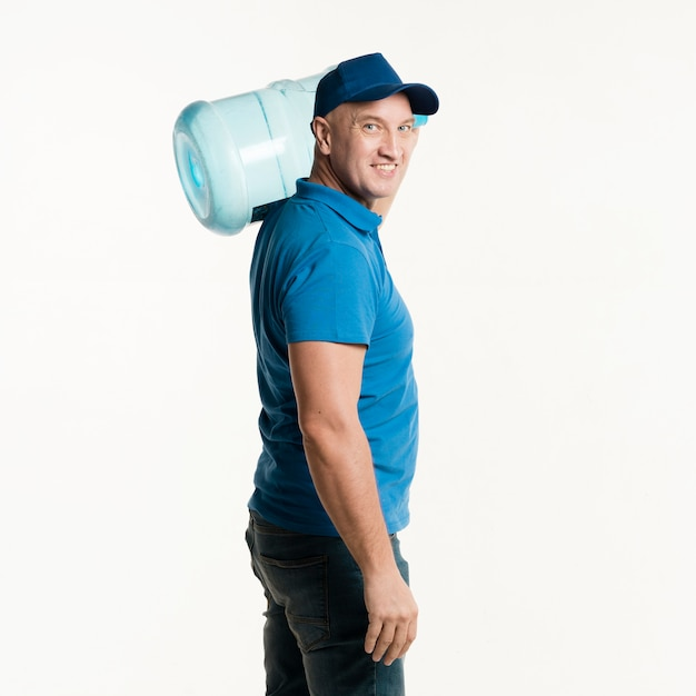 Smiley delivery man posing with water bottle Free Photo