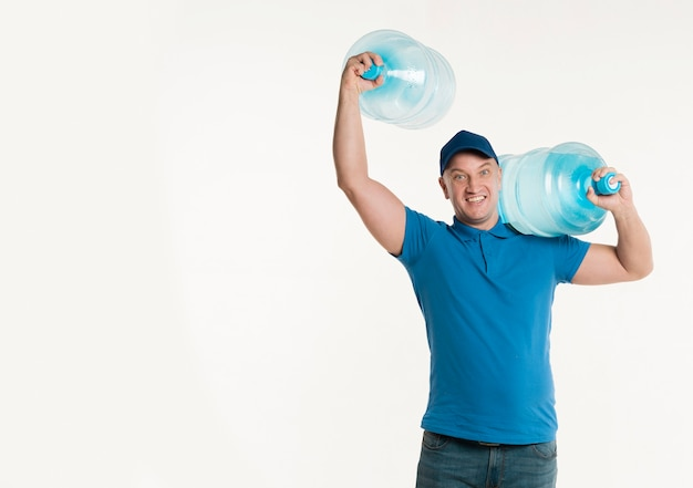 Smiley delivery man posing with water bottles and copy space Free Photo