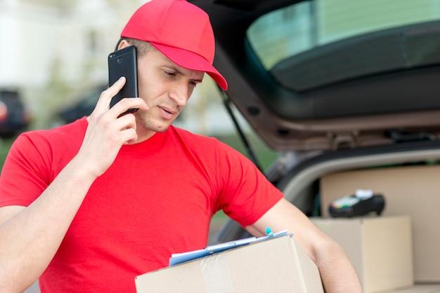 Uomo di consegna di smiley con telefono Foto Gratuite