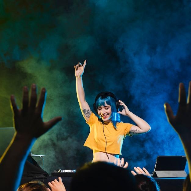 Smiley dj woman having fun with crowd Free Photo
