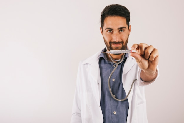 Smiley doctor posing with thermometer Free Photo