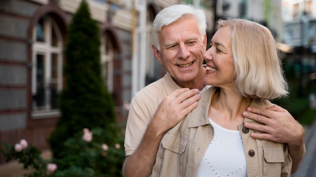 Smiley elder couple posing together while taking a walk in the city Free Photo