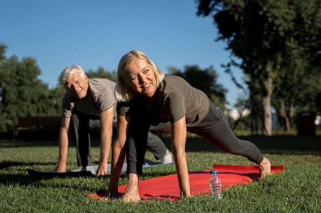 Smiley elder couple practicing yoga outdoors Free Photo